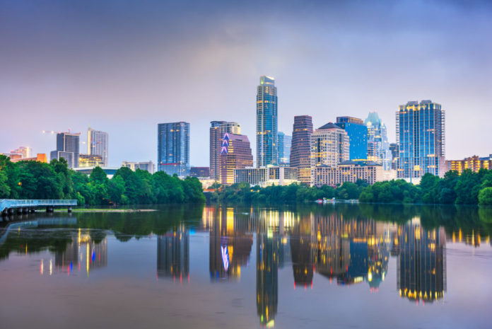 Austin, Texas, USA downtown skyline on the Colorado River at night. Find out how to get a free trip there.