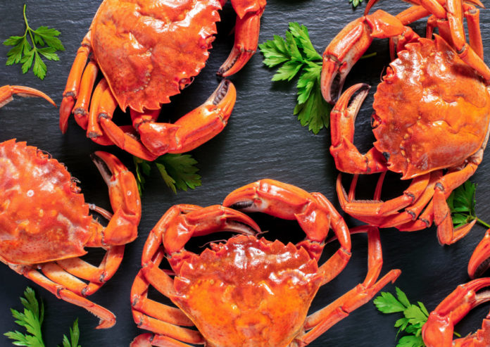 pile of fresh boiled crabs with greens and lemon on slate. Find out how to get your own crabs in Bluffton, SC