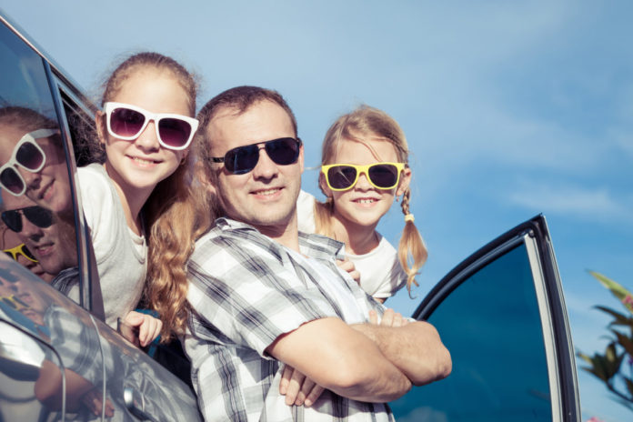 Happy family getting ready for road trip on a sunny day. Find out how to win one worth $3,000