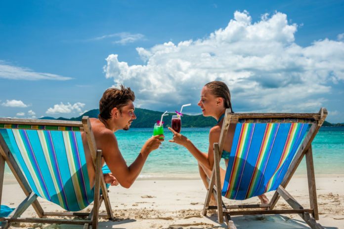Couple in loungers clinking their glasses on a tropical beach at Thailand. Learn how to stay a Thai beach hotel for free