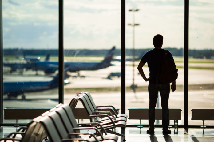 Silhouette of a man waiting to board a flight. LEarn how to get free airfare