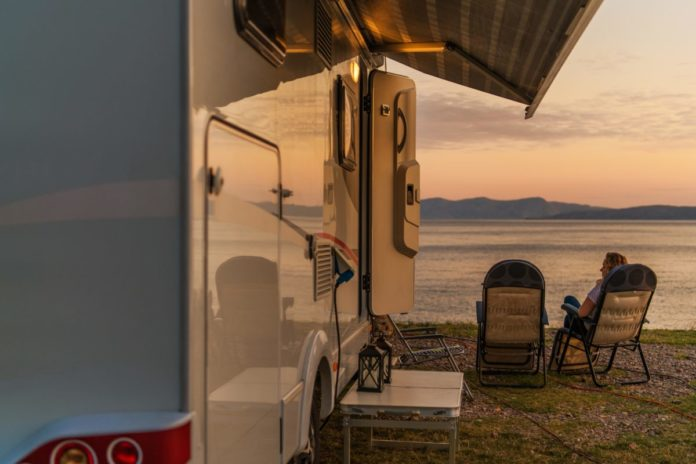 Campground Pitch Scenery. RV Camper Van In the Recreational Vehicles Park. Woman Relaxing on a Chair in Front of Her Camper Van. Find out how to win a free RV