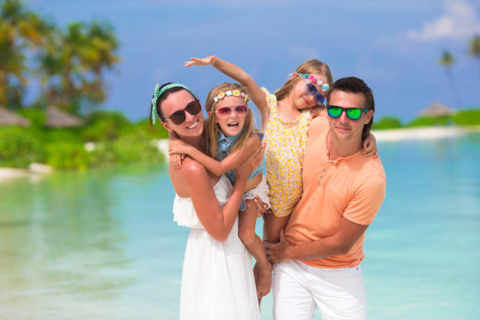 Happy beautiful family on a beach during summer vacation. Submit a family vacation photo to win a free VRBO vacation home stay.