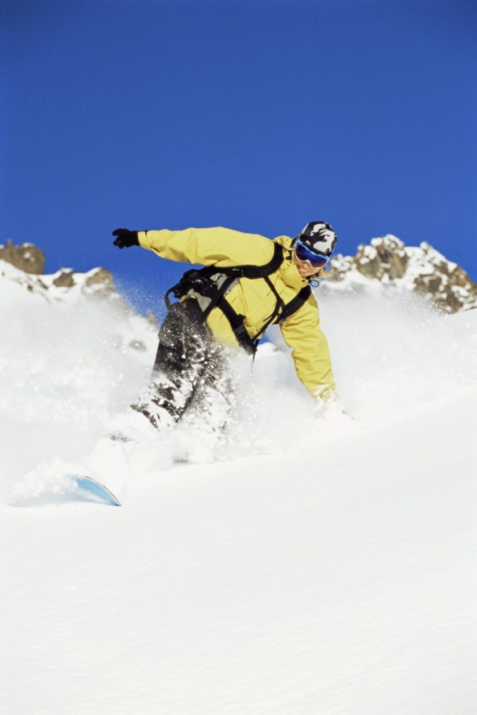 A picture of a woman snowboarding. Find out how to get a snowboard for free!