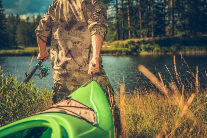 Caucasian Fly Fisherman Wearing Camouflage with Kayak Going Toward the River. Enter Paddling.com - Vibe Kayaks Sweepstake to win a free fishing kayak