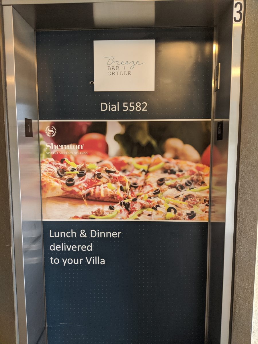A picture of an elevator with an advertisement for dining at Sheraton Vistana Villages Resort in Orlando FL