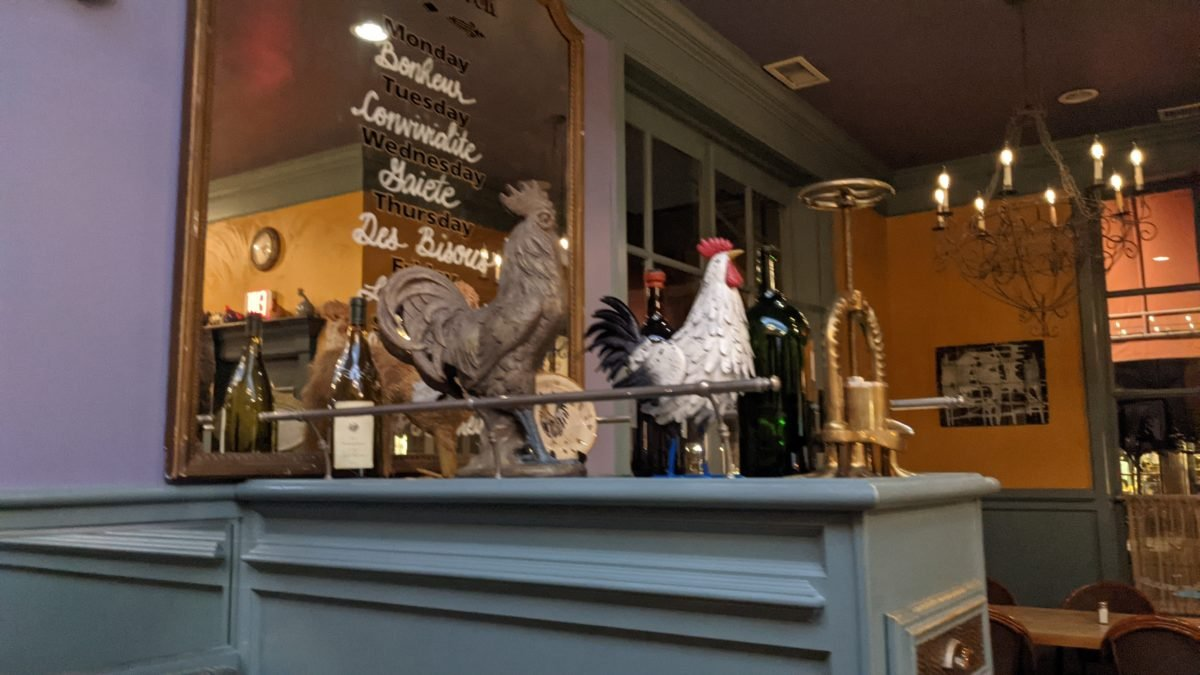 Rooster decor & the name of the days of the week in French are part of the decor at Williamsburg's Blue Talon Bistro