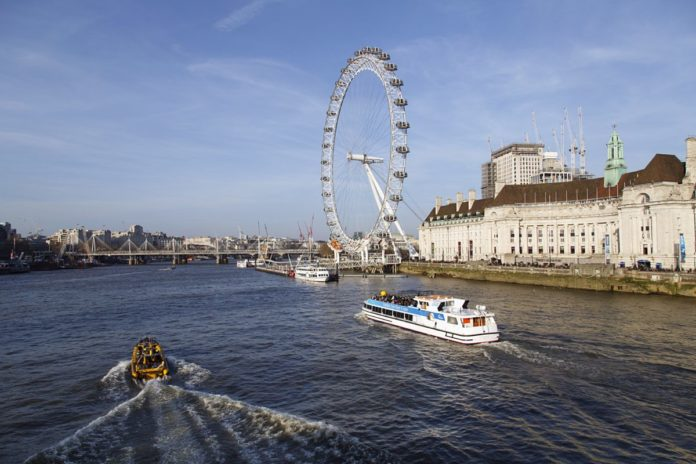 London Eye River Cruise boat passes the Millennium Wheel on the Thames River. Cruising the Thames is a leisurely way to view the new and historic buildings along the embankment on the way to Greenwich. Learn how to save money on this cruise with a discount price.