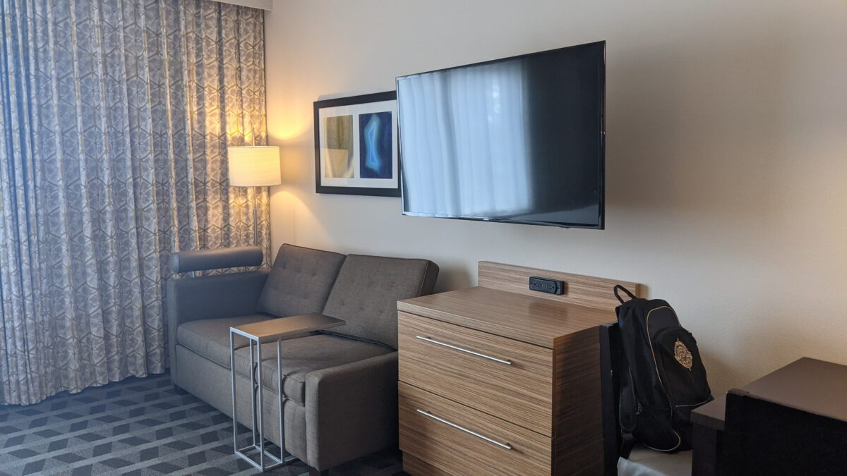 The living room areas have a large TV and sofa at TownPlace Suites Orlando International Drive near SeaWorld