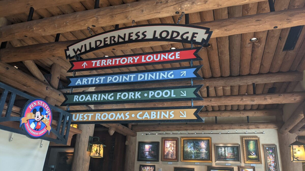 A picture of a sign pointing to how to get to Artist Point character dining and Roaring Fork quick service food at Wilderness Lodge in Walt Disney World
