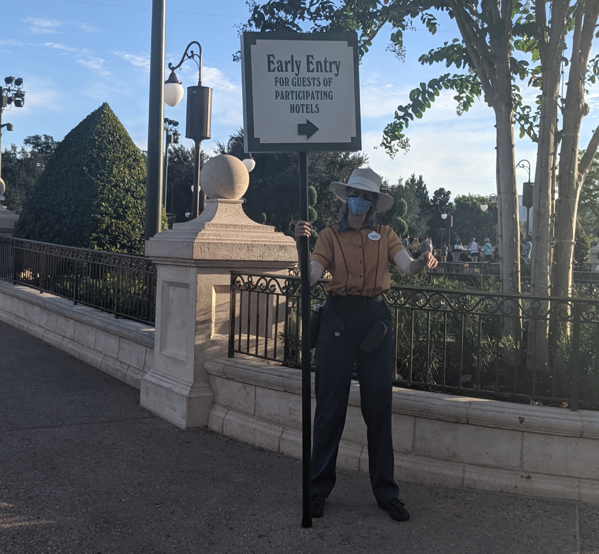 """Magic Kingdom Cast Member holding a sign that says """"Early Entry For Guests of Participating Hotels"""""""