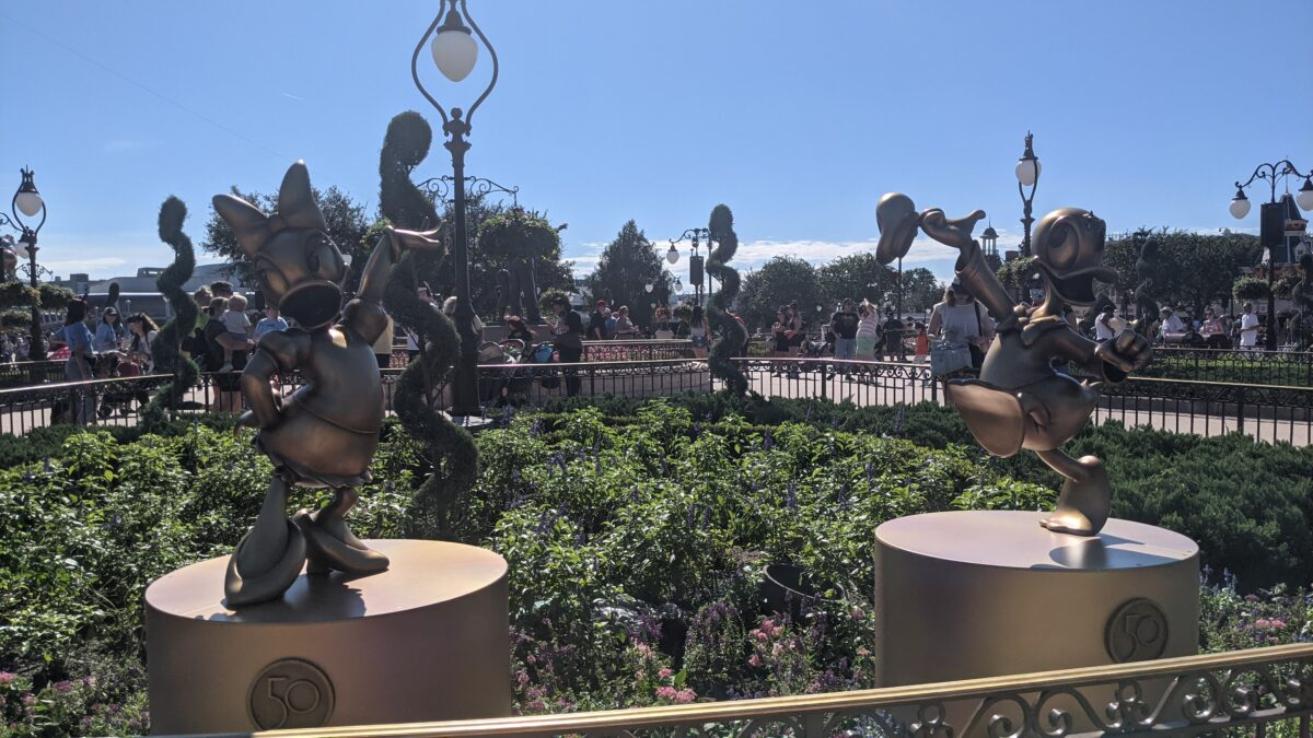 Walt Disney World 50th Anniversary Gold Statues are spread throughout the theme parks, like these statues of Donald & Daisy at Magic Kingdom