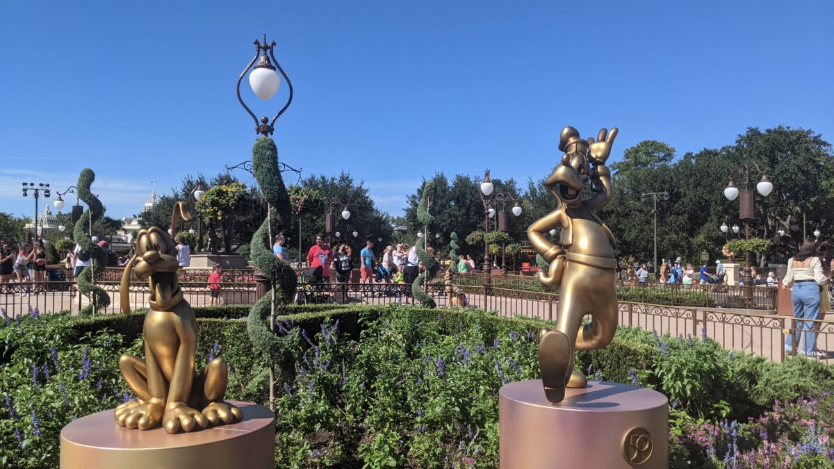 The Walt Disney World 50th Anniversary features gold statues of classic characters like Pluto and Goofy
