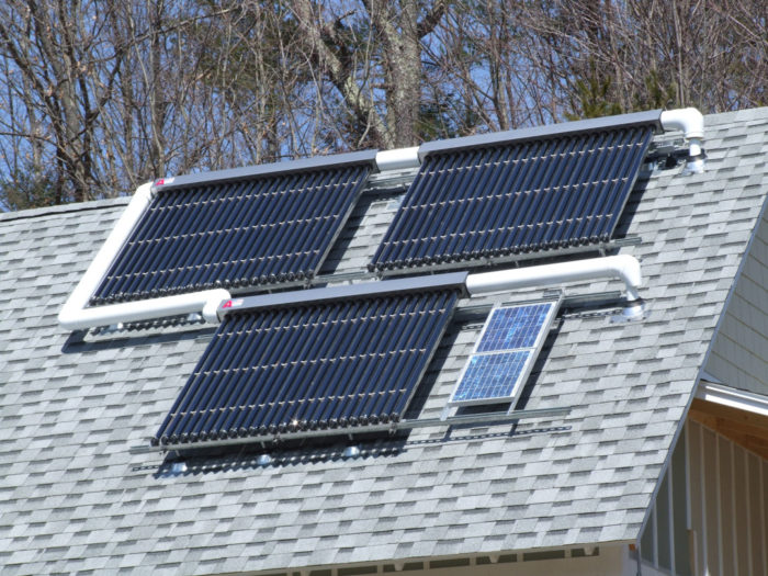 This Massachusetts house has a generously sized solar thermal system with three large evacuated-tube collectors. The small PV panels at the lower right ...