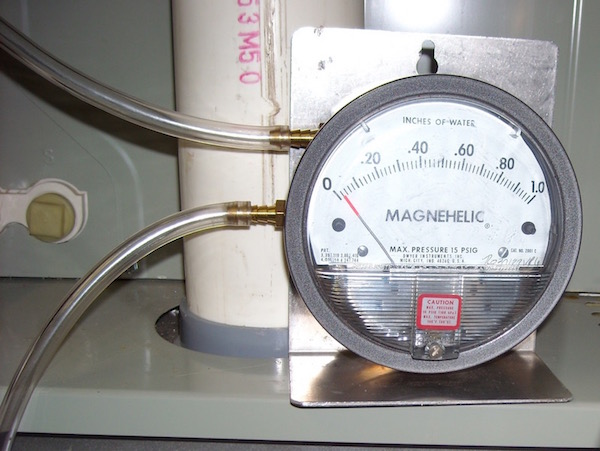 Measuring pressure drop with a magnehelic gauge  [Photo credit: Energy Vanguard]