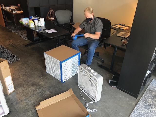 Luke assembling a high-MERV portable air cleaner for the Energy Vanguard office