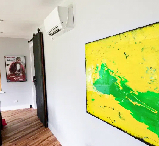 Photograph of a painting and a minisplit head on the wall.