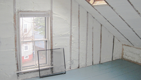 Photo showing an attic insulated with spray foam.