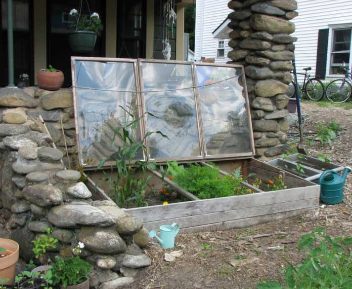 A cold frame can be constructed from materials you can easily find. This one is made from lumber and some old windows.