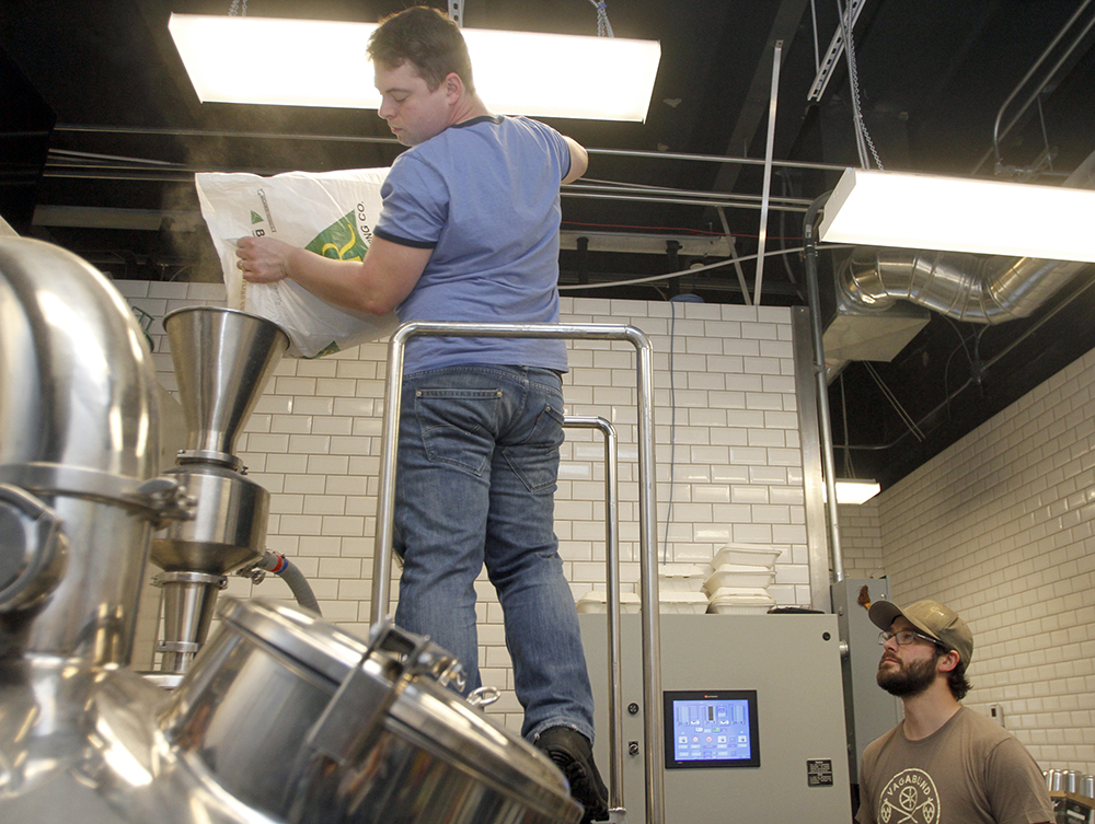 Forager Brewery head brewer and co-owner Austin Jevne, right, and Erik Mell, a brewmaster in Berlin, Germany, combine grains and hot water in a process called mashing.