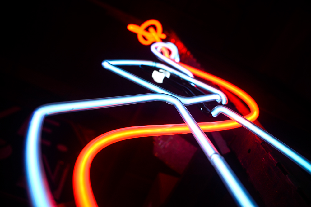 An argon (blue) and neon (red) filled glass sign flickers to light // Photo by Dan Murphy