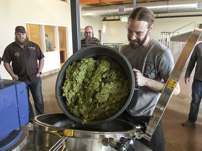 A brewer from Odell adds hops to the Peaks & Prairies beer