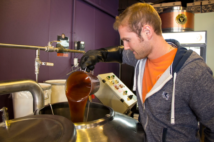 Customer pouring malt extract into the brew kettle // Photo by Brian Kaufenberg