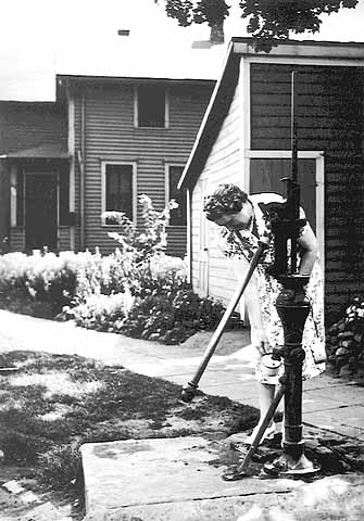 Woman pumping water from pump on Bohemian Flats, Minneapolis // Photo courtesy of Minnesota Historical Society