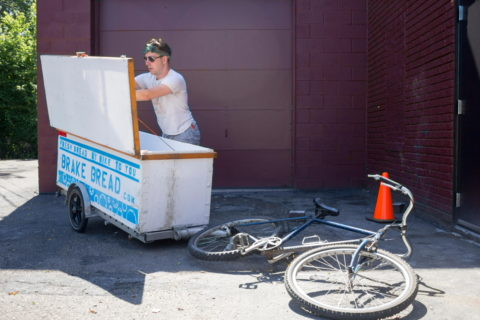 Bike delivery rider Adam Patterson loads the delivery trailer at Brake Bread // Photo by Brian Kaufenberg