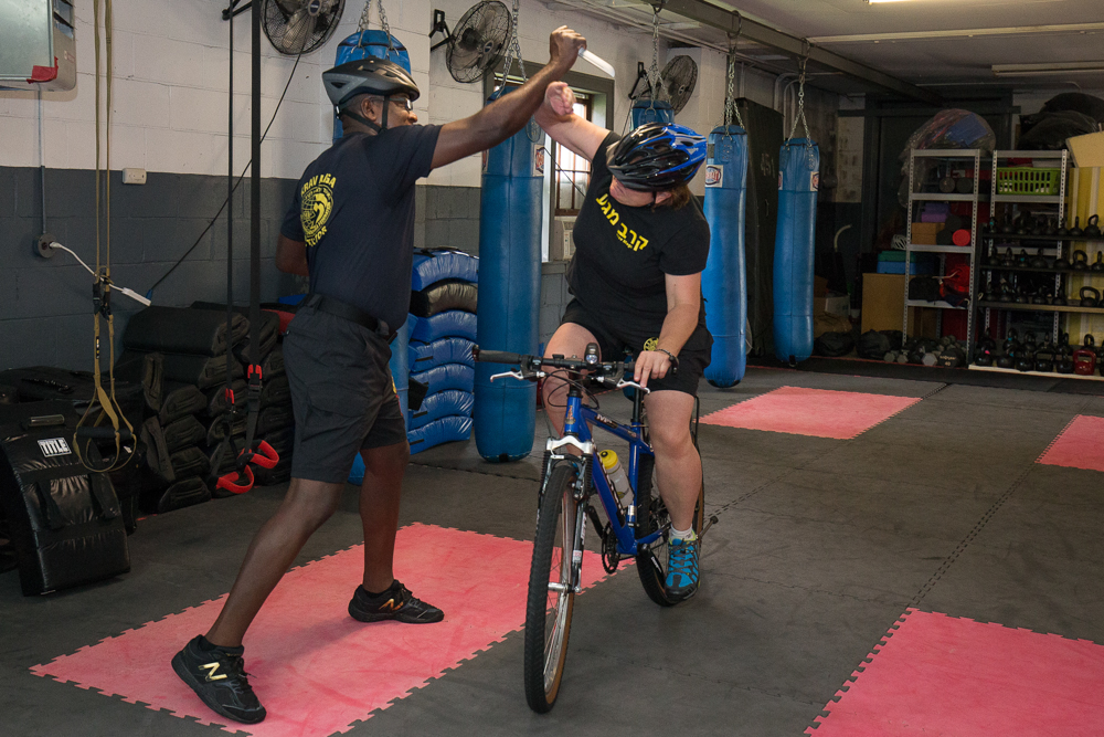 Krav Maga Minneapolis owner Gail Boxrud demonstrates how to fend off a knife attack while biking // Photo by Ryan Siverson