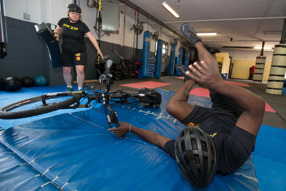Dante Pastrano of Krav Maga Minneapolis shows the proper way to fall from a bike // Photo by Ryan Siverson
