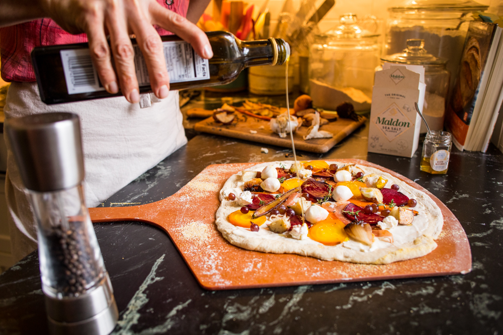 Zöe François drizzles olive oil over a pizza before putting it into the oven // Photo by Tj Turner