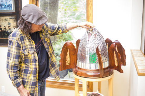 Woodworker Mark Laub rotates the leaded glass dome of an ornate cabinet to reveal a bottle of Absinthe // Photo by Tj Turner