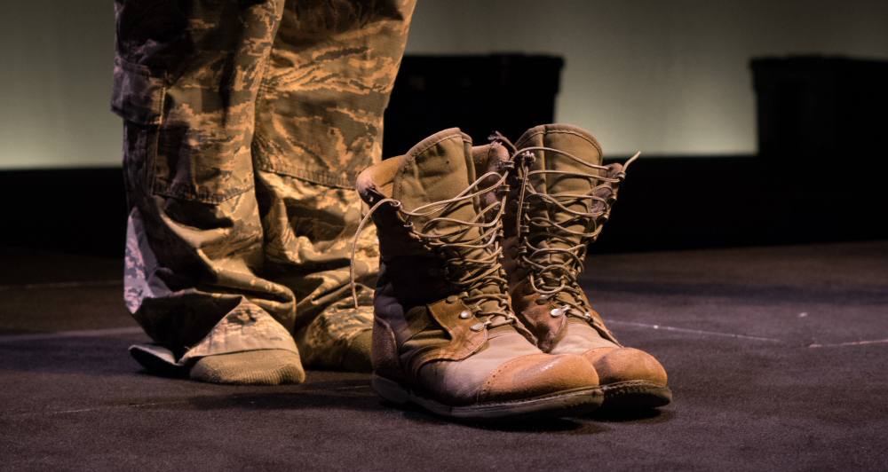 "One of the actresses stands behind her boots in the The Telling Project's production of ""She Went to War"" in the Guthrie's Dowling Studio. // Photo by Gaea Dill-D'Ascoli"