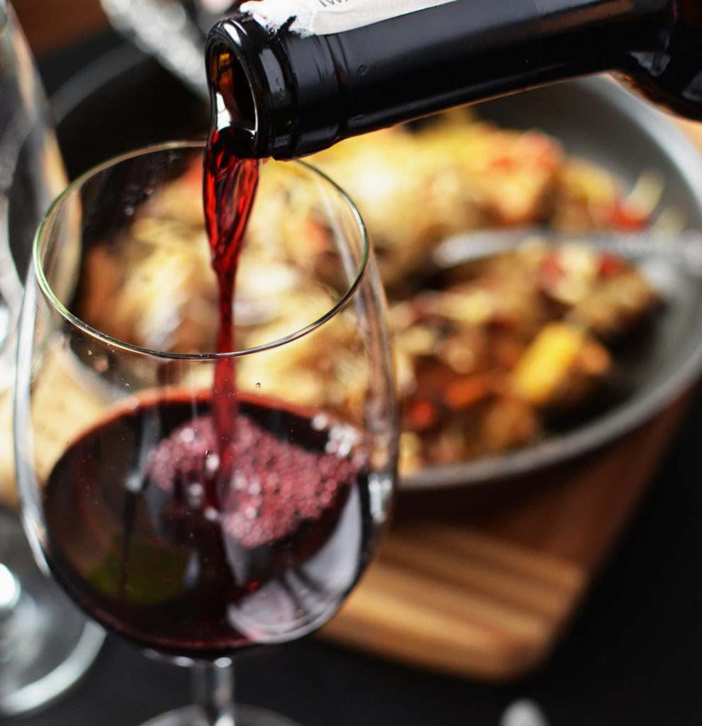 Red wine being poured into a glass at dinner // Photo via Pexels
