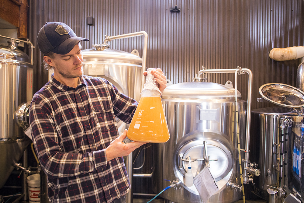Jeff examines one of his experimental brews // Photo by Tj Turner