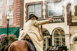 An actor fires his gun during the annual re-enactment in Northfield, MN // Photo via the Defeat of Jesse James Day Facebook