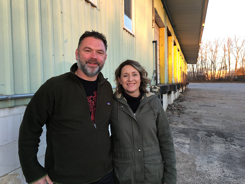 Steve Finnie (right) and Dawn Finnie (left) stand arm in arm in front of their newly purchased property and future home of Little Thistle Brewery in Rochester, Minnesota // Photo by Joseph Alton, The Growler