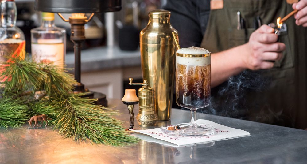 Nathaniel Smith of Spoon and Stable put his finishing touches on the Rum and Julmust cocktail by burning a stick of cinnamon // Photo by Kevin Kramer