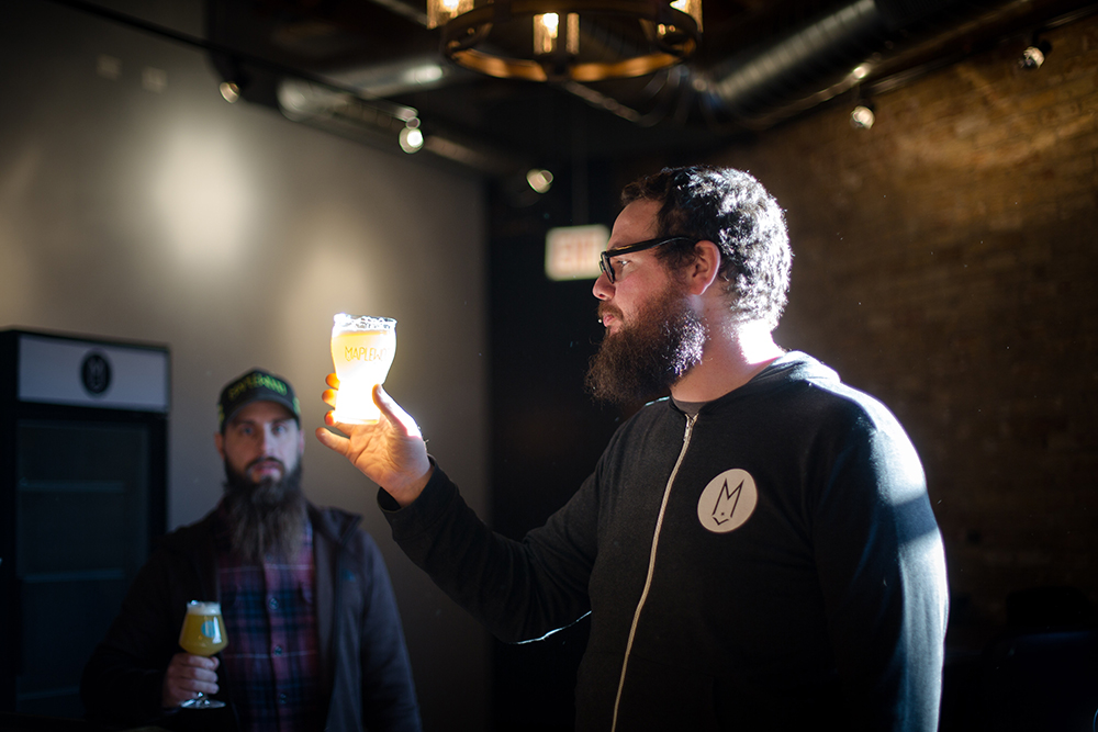 Adam Smith (right) and Adam Cieslak (left) of Maplewood Brewing Company inspect their brew in the light // Photo courtesy of Maplewood Brewing Company