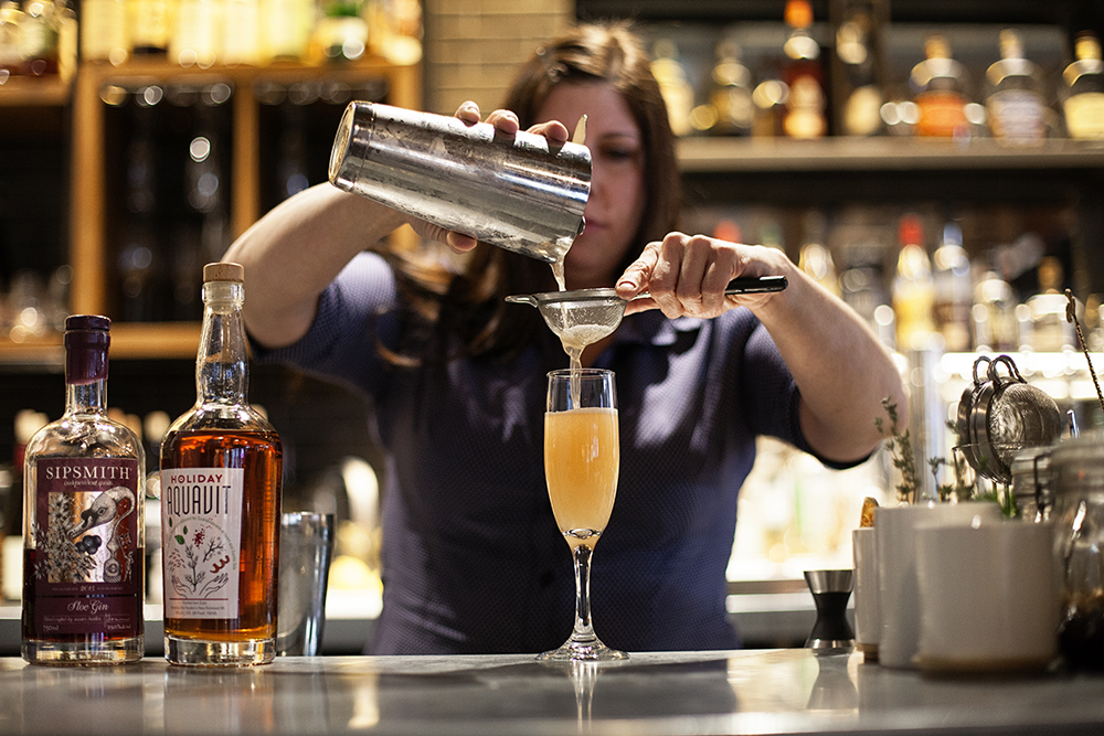 "Trish Gavin, a Hewing Hotel bartender, double straining her ""I'm Trying to Break Your Heart"" cocktail into a Champagne flute // Photo by Katie Cannon"
