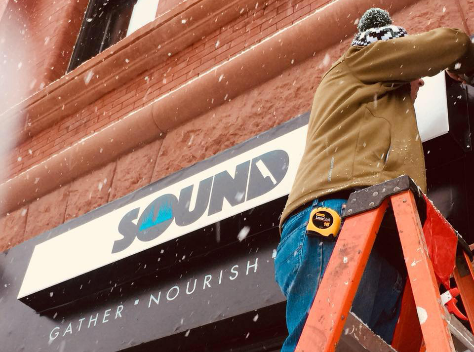 Putting up the sign outside of SOUND Duluth in the snow // Photo courtesy SOUND Duluth Facebook