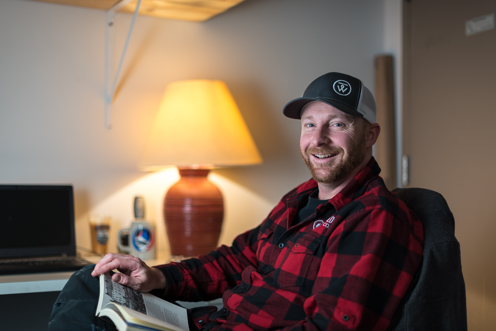 Derek Allmendinger, of Unmapped Brewing Company, enjoys a book in his office // Photo by Kevin Kramer