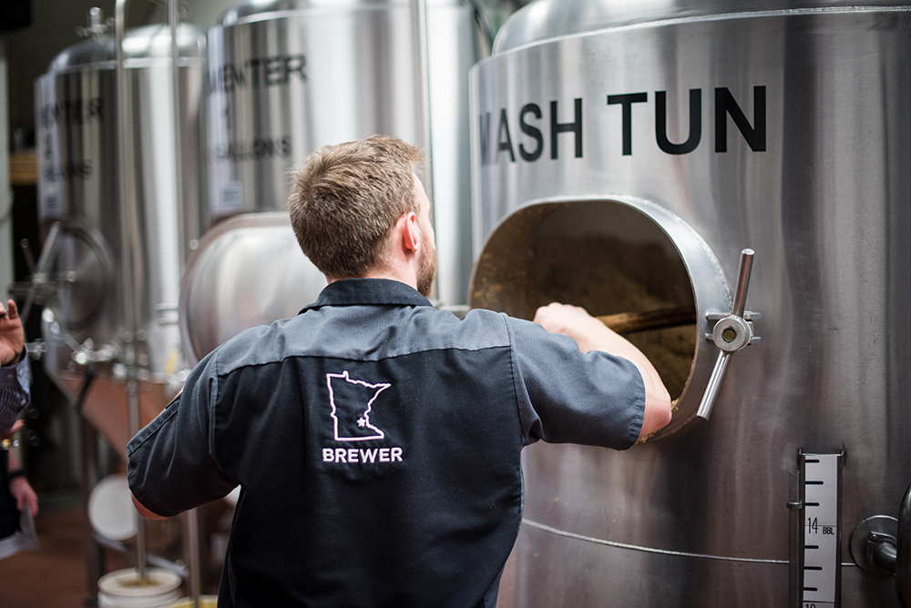 A Town Hall Brewery employee rakes out the Mash Tun during a brew day // Photo by Kevin Kramer