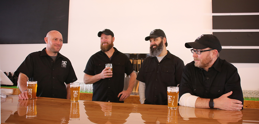 From left to right, Scott Larson, co-founder and taproom manager; Scott Schlink, assistant brewer; Ryan Seabright, CFO; and Chris Larson, head brewer and CEO // Photo by Louis Garcia