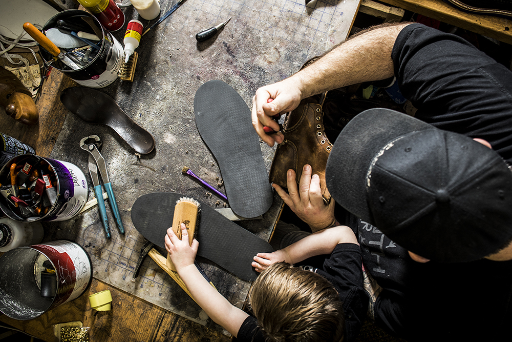 Pamazi working on a fresh sole with the help of his son // Photo by Tj Turner