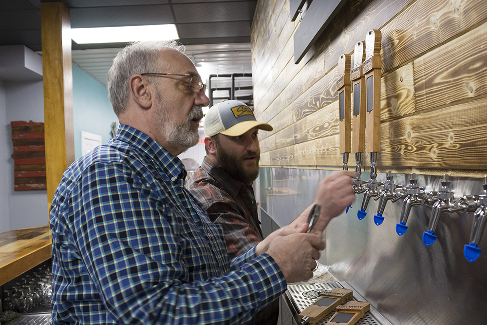 Doug Fenske, left, and Caleb Fenske, right—a father and son duo—work on the taps in their soon to open Lost Sanity Brewing in Madelia, Minnesota // Photo by James Figy