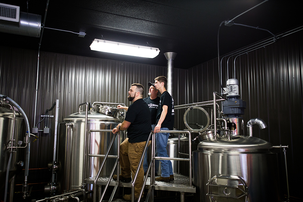 John Thrailkill, left, James Burt, right, and Bill Burt in middle back stand on the brew deck at Rustech Brewing in Monticello, Minnesota // Photo by Aaron Davidson