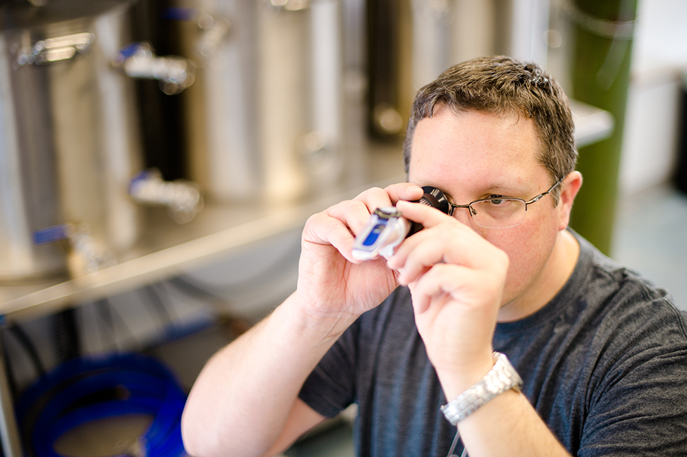 "Scott Mouw, Dr. Geiger's business partner, uses a refractometer to get an original gravity reading of sterile wort that will be added to their yeast ""traps"" // Photo by Sarah Bird"