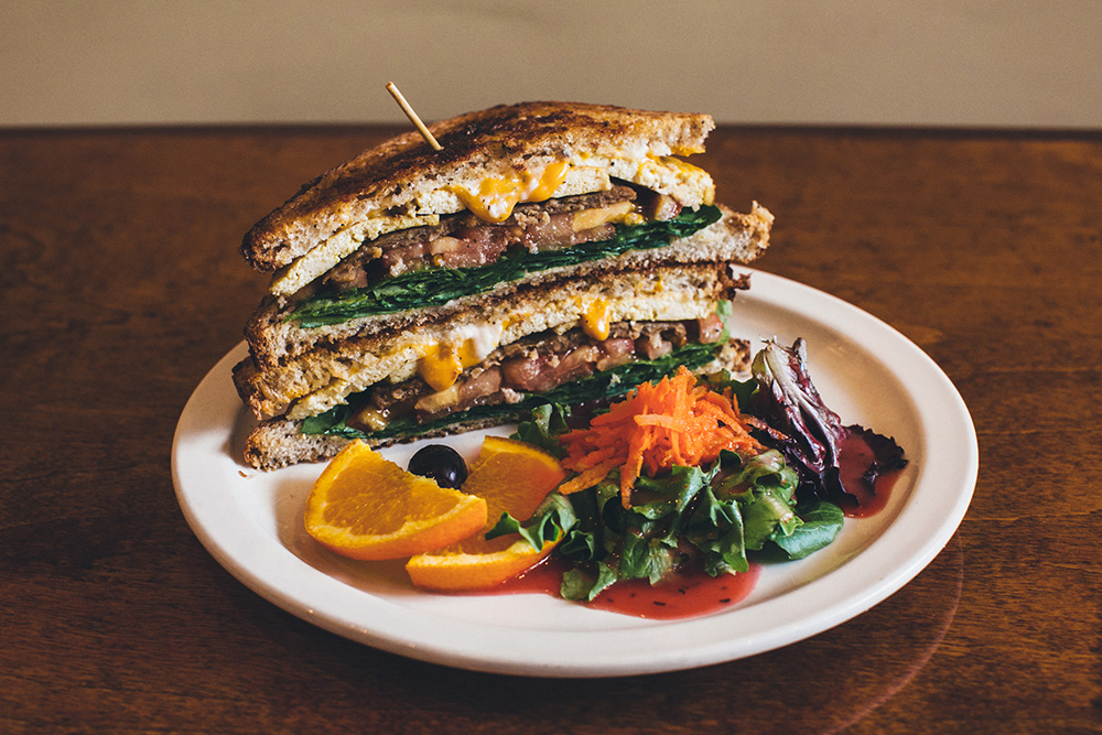 "The Detroit Vegan Soul Breakfast Sandwich with pan fried tofu ""egg,"" veggie sausage, veganaise, spinach and tomato on multi-grain bread which is served with a side salad // Photo courtesy Adwater Media"